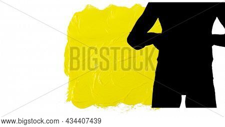 Mid section of silhouette of female handball player against yellow paint brush strokes. sports and competition concept