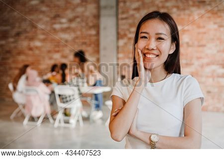 Close up of a happy mid aged asian woman standing looking at camera with group of multiethnic women sitting at the table indoors during seminar only for women, feminism concept