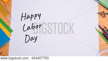 Happy labor day text over white paper against multiple school equipment on wooden table. labor day celebration concept