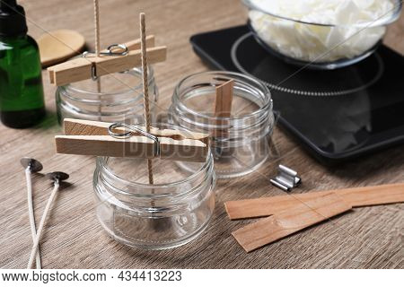 Glass Jars With Wicks And Clothespins As Stabilizers On Wooden Table. Making Homemade Candles