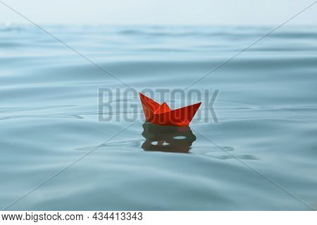Orange Paper Boat Floating On Water Surface