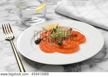 Salmon Carpaccio With Capers, Microgreens And Lemon Served On White Marble Table
