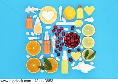 Cranberry and citrus fruit with orange and lemons, ingredients for skincare beauty treatment. Plant based anti ageing health care concept. On blue background.