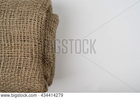 Folded Burlap Fabric Textile On White Background, With Copy Space For Text Or Design Use. Crumpled F