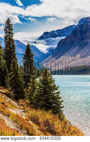Red, yellow and orange autumn grass on the shores of the Bow Lake. The Rockies of Canada. Lake cold glacial water is rippled. The concept of active, environmental and photo tourism