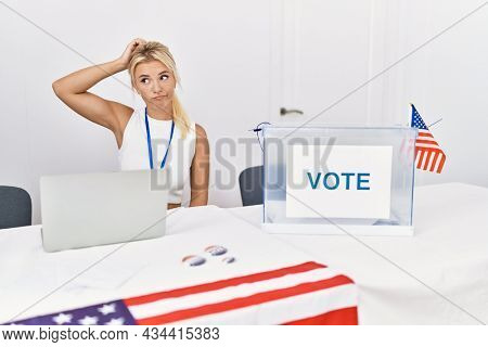 Young caucasian woman at america political campaign election confuse and wondering about question. uncertain with doubt, thinking with hand on head. pensive concept.