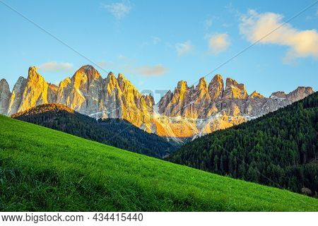 Sunset. Dense forests grow on the mountain slopes. The majestic cliffs of the Dolomites rise picturesquely into the sky. Dolomites on a sunny autumn day.