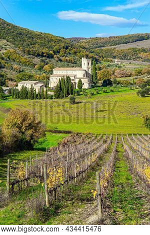 Charming abbey among vineyards and fields. Sunny day at the beginning of winter. Abbey of Sant Antimo. The magical beauty of the province of Tuscany. Magnificent Italy.