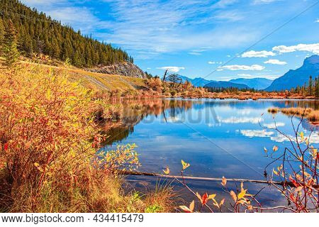 Indian summer in the Rocky Mountains. Red, yellow and orange foliage of the autumn forest. The smooth cold water of Lake Vermillon reflects the snow-white clouds