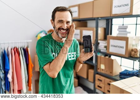 Middle age man with beard wearing volunteer t shirt holding smartphone hand on mouth telling secret rumor, whispering malicious talk conversation