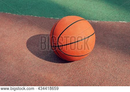 Side View Of Orange Ball For Basketball Lying On The Rubber Sport Court.