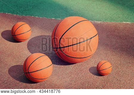 Side View Of Orange Balls For Basketball Lying On The Rubber Sport Court.