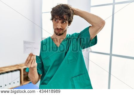 Young hispanic doctor man holding covid record card confuse and wondering about question. uncertain with doubt, thinking with hand on head. pensive concept.