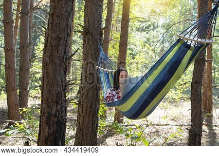 Freelance And Working At Nature. Freelancer Woman Works At Notebook While Lying On The Hammock In Th