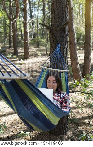 Freelance And Working At Nature. Smiling Woman Freelancer Works At Notebook While Lying On The Hammo
