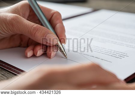 Low Angle Closeup View Of A Female Hand Signing A Contract Or Document.