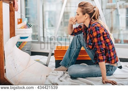 Portrait of a Beautiful Serious Engineer Woman Thinking about Apartment Construction Plan. House Renovation.