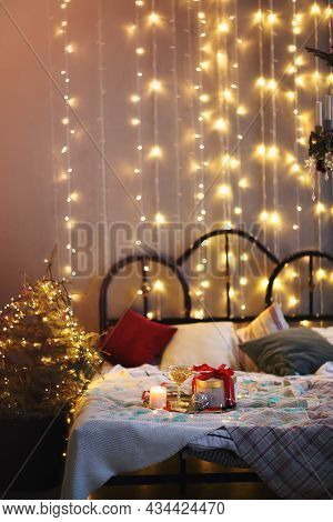 Tray With Decorations And Gift Box Placed On Comfortable Bed In Cozy Bedroom Decorated For Christmas