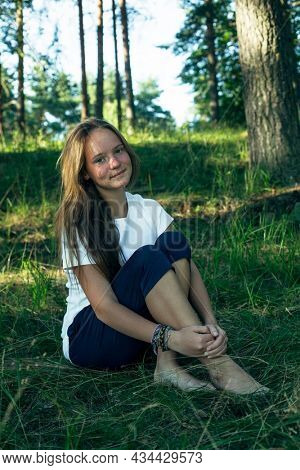 Teengirl sitting on the green grass in the summer park.