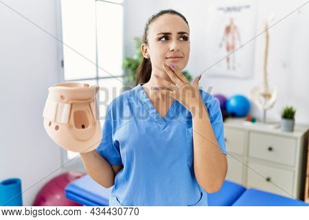 Young physiotherapist woman holding cervical neck collar at medical clinic serious face thinking about question with hand on chin, thoughtful about confusing idea
