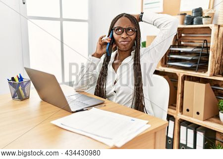 Black woman with braids working at the office speaking on the phone confuse and wondering about question. uncertain with doubt, thinking with hand on head. pensive concept.