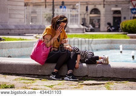 Trieste, Italy - May, 31: Mom And Little Daughter Sitting On The Bench. Mom Talks On The Phone While