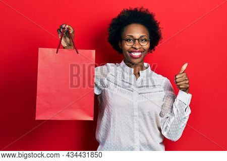 Young african american woman holding shopping bags smiling happy and positive, thumb up doing excellent and approval sign