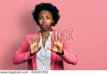 African american woman with afro hair wearing business jacket moving away hands palms showing refusal and denial with afraid and disgusting expression. stop and forbidden.