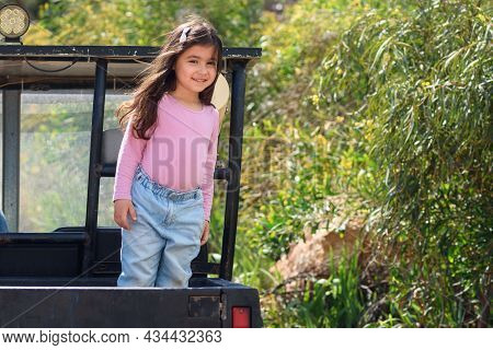 Smiling Child Having Fun In The Back Of Pickup Truck Enjoying The Road Trip In Country Side. Little