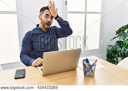 Young hispanic man with beard working at the office with laptop surprised with hand on head for mistake, remember error. forgot, bad memory concept.