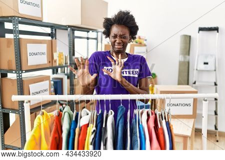 African young woman wearing volunteer t shirt at donations stand disgusted expression, displeased and fearful doing disgust face because aversion reaction. with hands raised