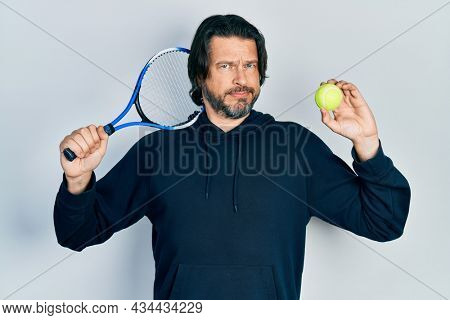 Middle age caucasian man playing tennis holding racket and ball skeptic and nervous, frowning upset because of problem. negative person.