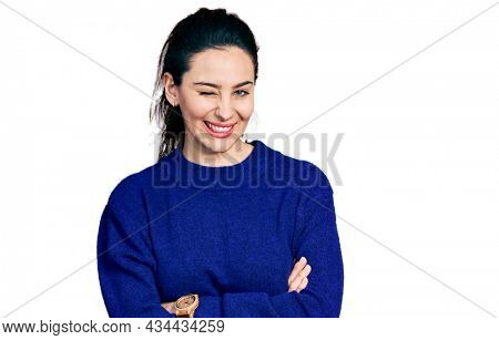 Young hispanic woman with arms crossed gesture winking looking at the camera with sexy expression, cheerful and happy face.