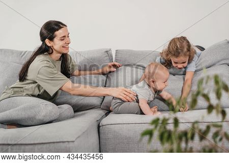 Cute Siblings Playing On The Sofa. Toddler Sister With Baby Brother Cuddling Up With Mother At Home.