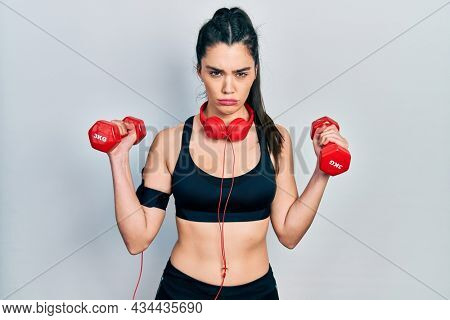 Young hispanic girl wearing sportswear using dumbbells skeptic and nervous, frowning upset because of problem. negative person.