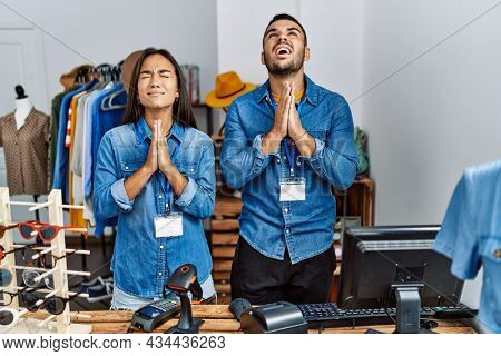 Young interracial people working at retail boutique begging and praying with hands together with hope expression on face very emotional and worried. begging.