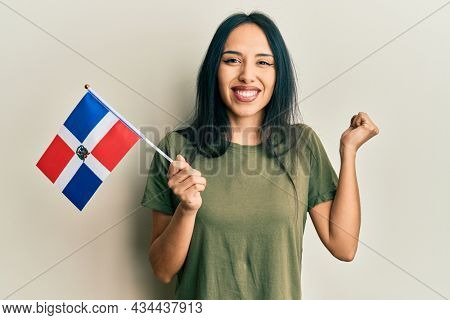 Young hispanic girl holding dominican republic flag screaming proud, celebrating victory and success very excited with raised arm