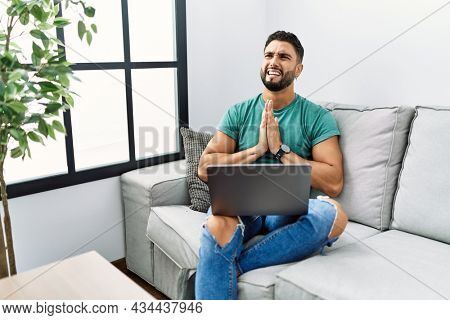 Young handsome man with beard using computer laptop sitting on the sofa at home begging and praying with hands together with hope expression on face very emotional and worried. begging.