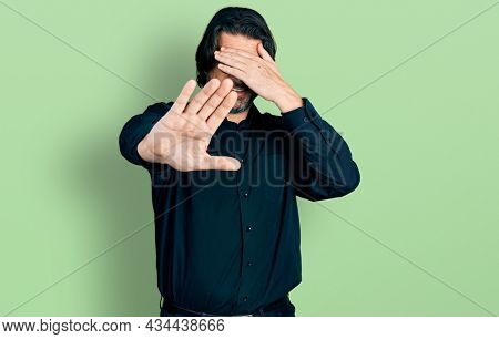 Middle age caucasian man wearing casual clothes and glasses covering eyes with hands and doing stop gesture with sad and fear expression. embarrassed and negative concept.