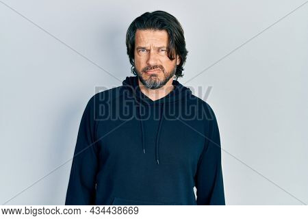 Middle age caucasian man wearing casual sweatshirt skeptic and nervous, frowning upset because of problem. negative person.