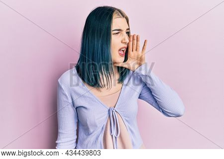 Young modern girl wearing casual jacket shouting and screaming loud to side with hand on mouth. communication concept.