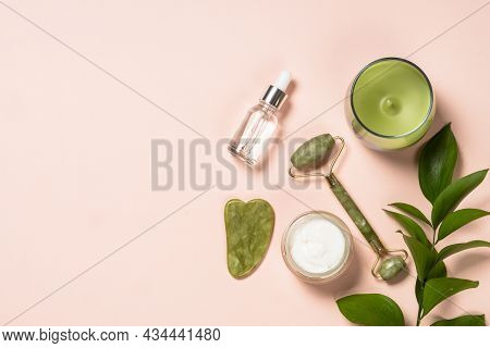 Jade Roller And Gua Sha Massager With Serum Bottle And Cream At Pastel Background. Anti-aging Therap