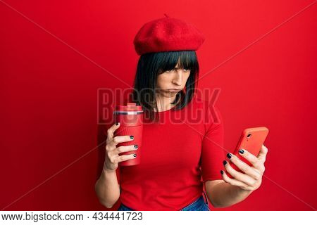 Young hispanic woman using smartphone and drinking a cup of coffee skeptic and nervous, frowning upset because of problem. negative person.