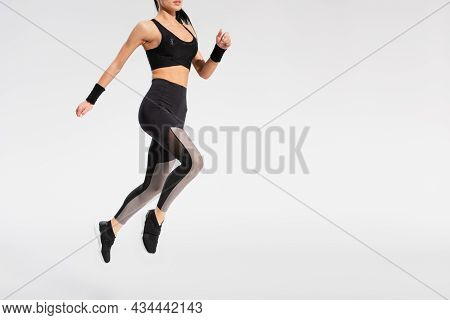 Partial View Of Young Woman In Sportswear Levitating On Grey
