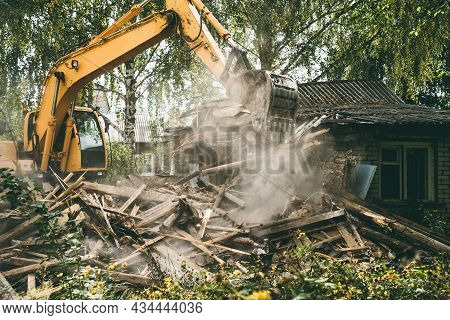 Demolition Of Old House. Excavator Breaks Building. City Development, Construction Of New Housing On