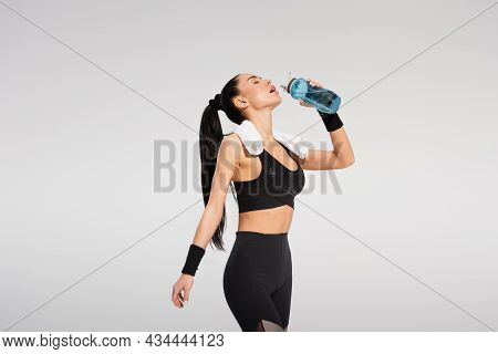 Young Sportswoman With Towel On Shoulders Holding Sports Bottle And Drinking Water Isolated On Grey