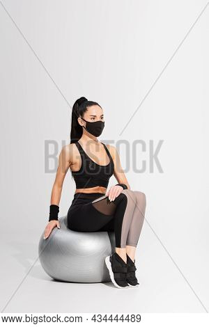 Young Sportswoman In Black Protective Mask Sitting On Fitness Ball On Grey