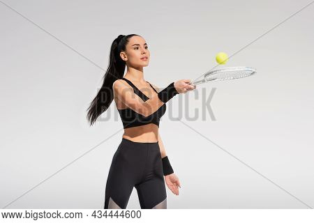 Young Sportswoman Holding Tennis Racket And Ball While Playing Isolated On Grey