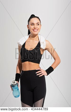 Happy Young Sportswoman With Towel On Shoulders Holding Sports Bottle While Posing With Hand On Hip