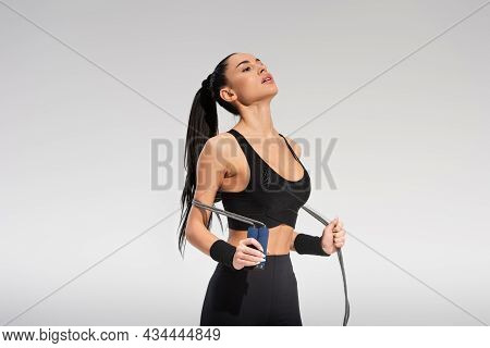 Young And Tired Sportswoman Holding Skipping Rope On Grey